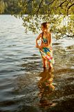 Young girl stands knee-deep in the water of a river and squeezes a wet dress stock image