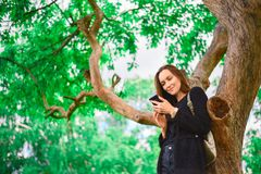 Young girl stands at a large green tree with a smartphone in her hands, communicates on the Internet messages, modern youth, copy stock image