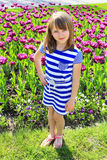 Young girl stands by lilac tulips Royalty Free Stock Images