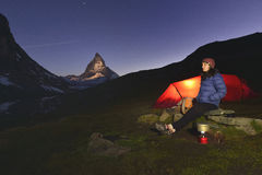 Young girl stands near her tent with the Matterhorn 4478m peak in background. Zermatt, Switzerland Stock Photo