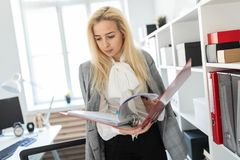 A young girl stands near a rack in the office and scrolls through a folder with documents. A slender young girl in a white blouse, gray jacket and dark trousers Stock Images