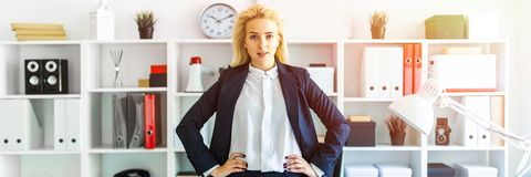 A young girl stands near a table in the office, with her hands on her hips. A slender young girl in a white blouse is working in the office. The girl has white royalty free stock image
