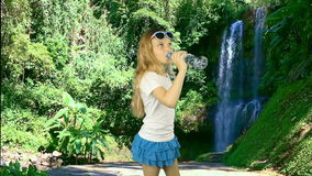 A young girl stands near a waterfall in the jungle and drinks crystal clear water from a bottle. A tropical forest and a. Huge waterfall. Healthy lifestyle stock video