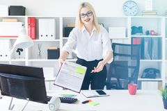 A young girl stands in the office at a computer Desk and stretches forward a pen and a document. royalty free stock photos