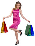 Young girl stands on one leg holding shopping bags Royalty Free Stock Images