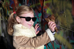 Young girl stands and posing near graffiti wall Royalty Free Stock Image