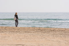 A young girl stands on seashore and looks at the sea Stock Image
