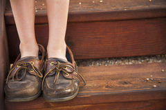 Young girl stands on a set of wooden stairs in a pair of shoes that are to large. A young child stands on wooden stairs in a pair of worn brown loafers that are Stock Photography