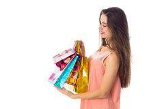 Young girl stands sideways and holding  bright beautiful bags isolated on white background Stock Image