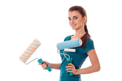 A young girl stands sideways and holding rollers for painting walls isolated on white background Royalty Free Stock Photography
