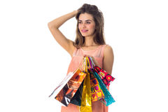 Young girl stands sideways keeps hand hair smiling while the other  holds the bright bags isolated on white background Royalty Free Stock Photos