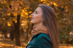 Young girl stands sideways in the Park and looks up close- Stock Image