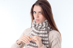 Young girl stands in  sweater and warm scarf is isolated on  white background Royalty Free Stock Image