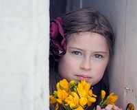 Young Girl Staring Into Camera, Holding Flowers, Between White Walls Stock Image