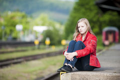 Young girl at the station. Sad girl on train station stock photography