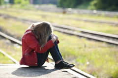 Young girl at the station. Sad girl on train station royalty free stock image