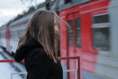 A young girl on the railway station. A young girl staying on the railway station in winter. The train passes she Stock Photos