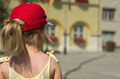 Young girl stood in street. Rear view of blond haired girl in cap stood on street, summer scene Royalty Free Stock Photography