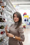 Young girl in store of dishes. Girl in supermarket near showcase with dishes royalty free stock photography