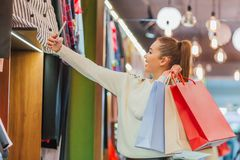 The young girl in the store is exhilarating. Keeping shopping bags photographed on the phone royalty free stock images