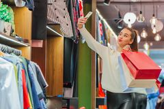 The young girl in the store is exhilarating. Keeping shopping bags photographed on the phone stock image