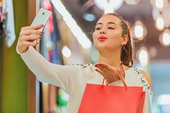 The young girl in the store is exhilarating. Keeping shopping bags photographed on the phone royalty free stock image
