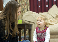 A young girl at storytime. An adorable little girl listening to a young woman telling a story royalty free stock images
