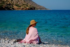 Young girl in a straw hat on the beach enjoying the beautiful views Royalty Free Stock Image