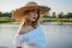 Young girl in straw hat posing outdoor Stock Photography