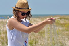 Young girl in a straw hat, sand in hands Royalty Free Stock Photos