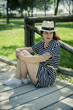 Young girl with straw hat sitting on a wooden bridge in a park i Stock Image
