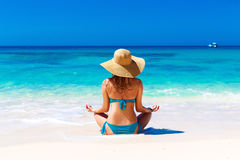 Young girl in a straw hat on a tropical beach. Summer vacation Royalty Free Stock Photo