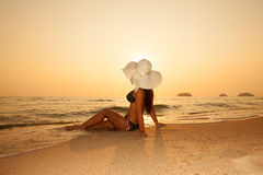 Young girl in a straw hat on a tropical beach at sunset. Summer Stock Photo