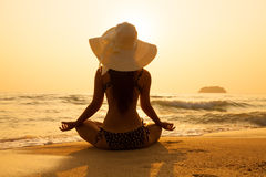 Young girl in a straw hat on a tropical beach at sunset. Summer. Vacation concept Stock Image