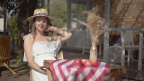 Young girl in a straw hat and white dress sitting at the small table and looking at the camera. Rural lifestyle. Leisure. On a beautiful summer day stock video