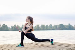 Young girl stretches her legs during training workout exercises Stock Photo
