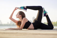 Young girl stretches at yoga pose during training workout outdoo Stock Photos