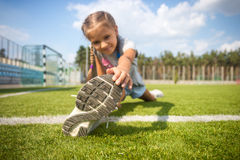 Young girl stretching on grass before running Stock Images