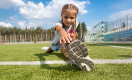 Young girl stretching legs on soccer field at sunny day Royalty Free Stock Photography