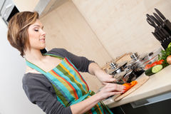 Young girl in striped apron cooks vegetables Stock Image