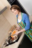 Young girl in striped apron slices vegetables Royalty Free Stock Photo