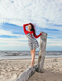 Young girl in striped dress on a beach Stock Image