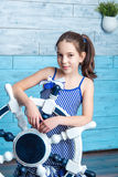 Young girl in striped dress with steering wheel royalty free stock image
