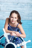 Young girl in striped dress with steering wheel royalty free stock photography