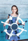 Young girl in striped dress with steering wheel stock photo