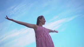 Young girl in a striped red and white dress. A girl stands against a blue sky, raising her hands up, a sign of freedom. Young charming girl in a striped red and stock footage
