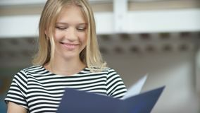 A young girl in a striped sweater holding a blue folder in her hand stock video footage