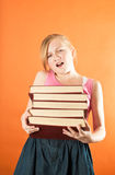 Young girl struggling to hold a pile of books Royalty Free Stock Photo