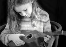 Young girl strumming instrument royalty free stock photos