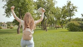 A young girl-student with a backpack on her back and notes in her hands is walking in the park. Rest during study. stock video footage